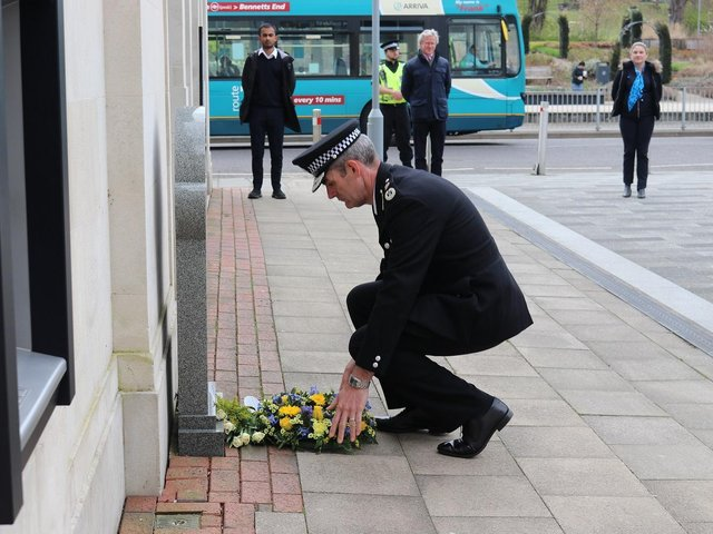Chief Constable Charlie Hall laying a wreath at the site of PC Mason's memorial stone in Bank Court