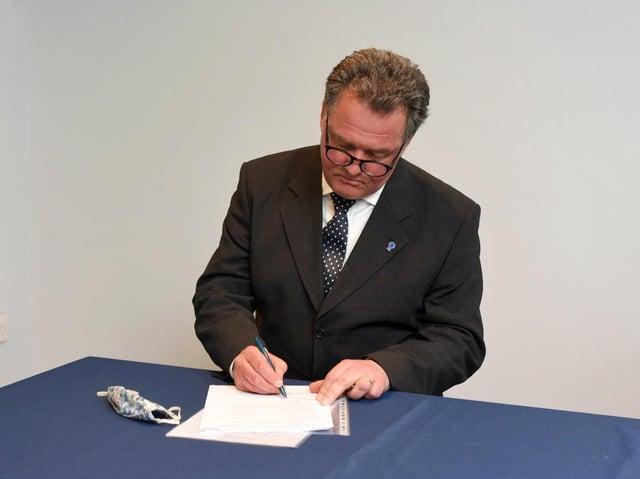 Mr Lloyd signing the oath