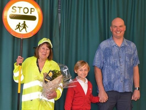 Pictured with lollipop lady Carole Hicks are Paul Allen (far right), who attended the school in 1981 when Carole first started in her role, and his son Elwood (middle) who attends the school