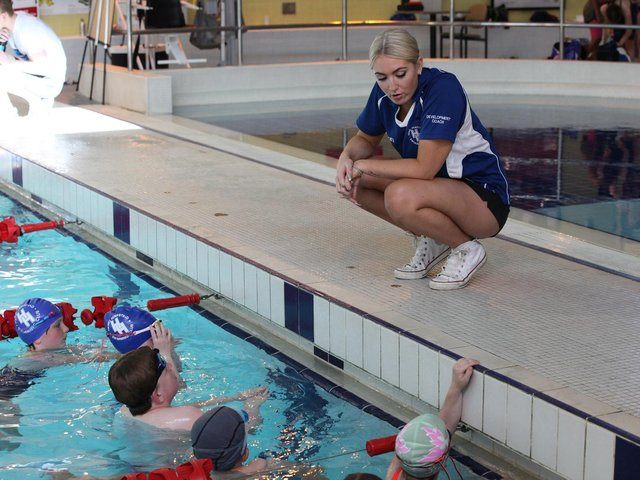 One of the club's coaches with some young swimmers